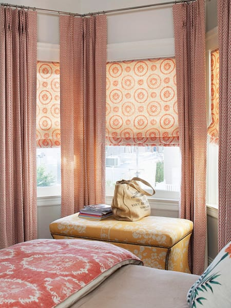 shades layered with curtains bring more depth to the window treatment