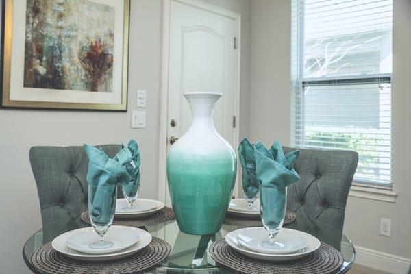 Dining table set with aqua colored vase and napkins, an example of Palm Beach style