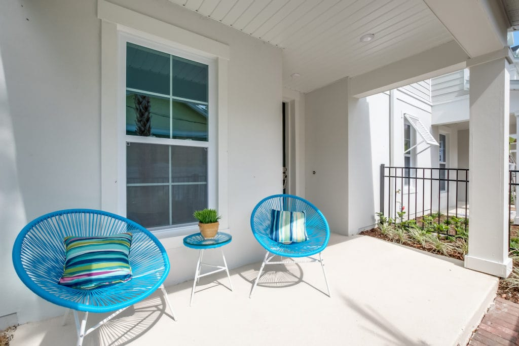 Aqua colored rattan on a white porch, an example of Palm Beach style