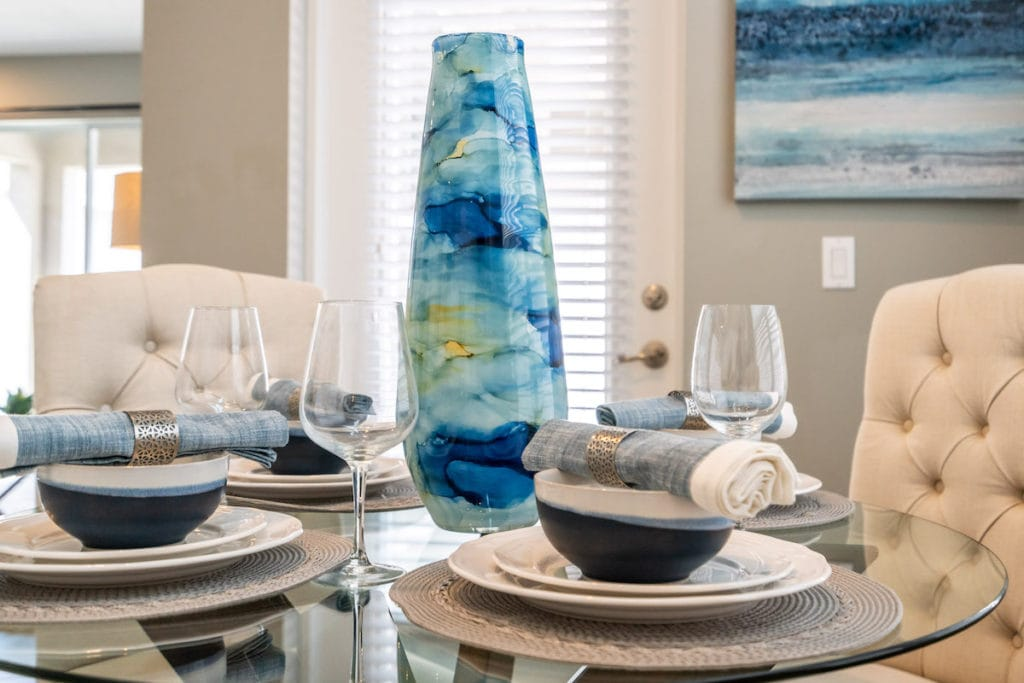 Tablescape with large aqua colored vase, an example of Palm Beach style