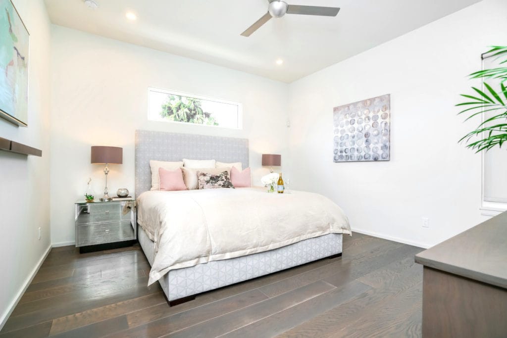 White bedroom with mirrored nightstand, an example of Palm Beach style