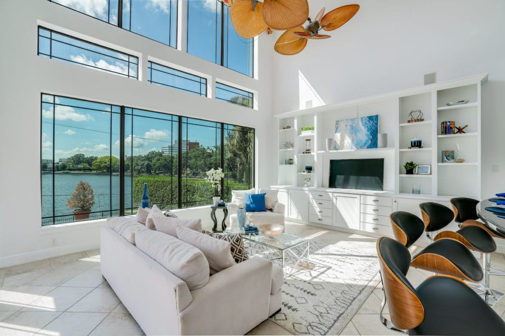 Bright white living room with large windows and tropical wicker ceiling fan, an example of Palm Beach style