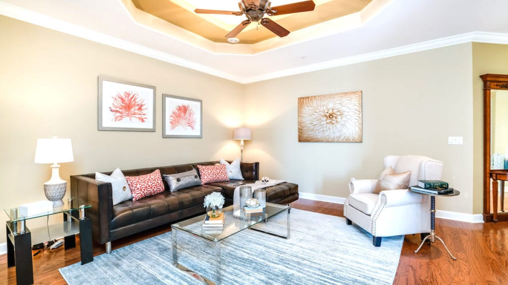 Neutral colored living room with coral accents, an example of Palm Beach style