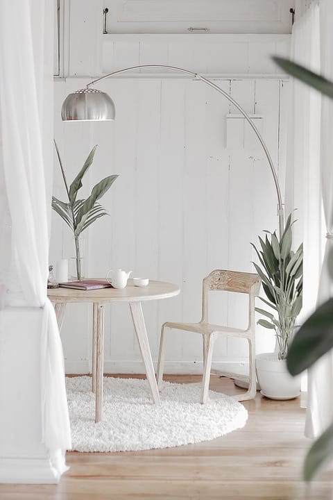 Minimal, all white room with white washed table and chair and a few plants