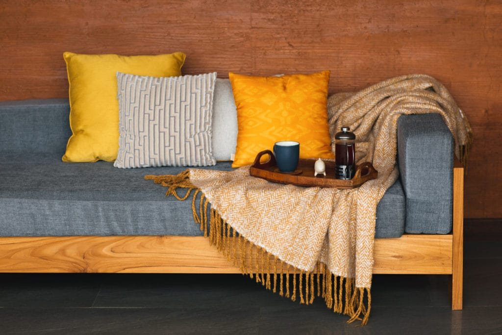A couch with wooden frame and gold throw pillows is an example of fall interior design trends