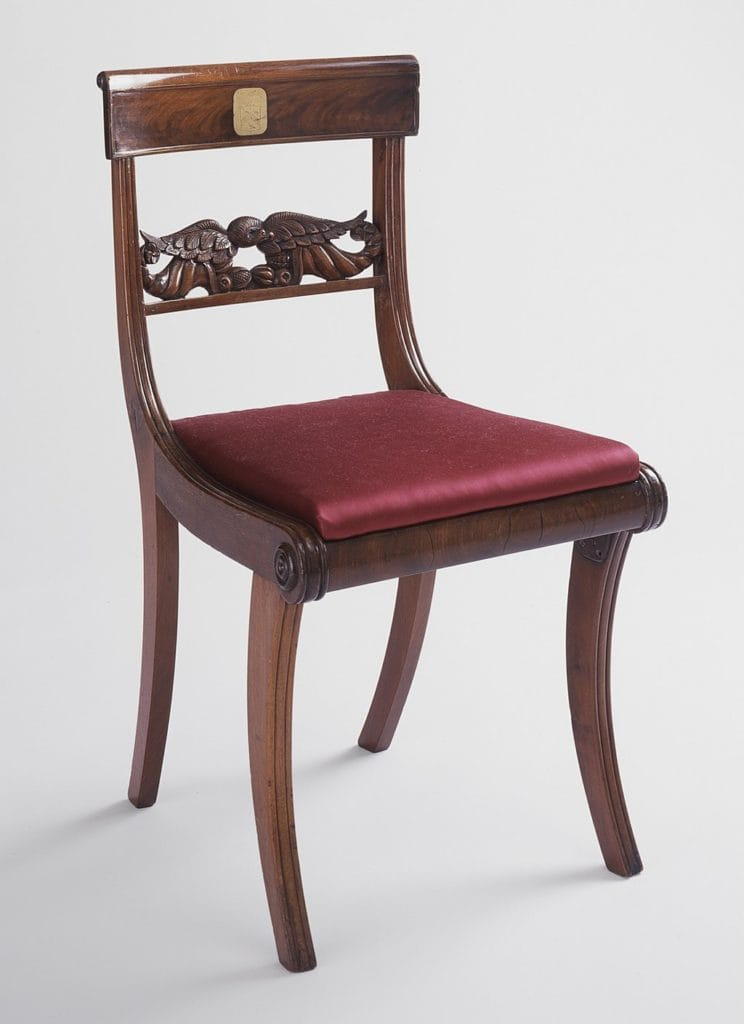 Wooden klismos chair with red seat cushion