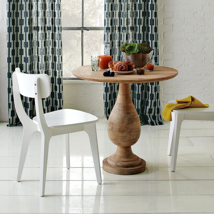 White klismos dining chairs from West Elm paired with a brown wooden table