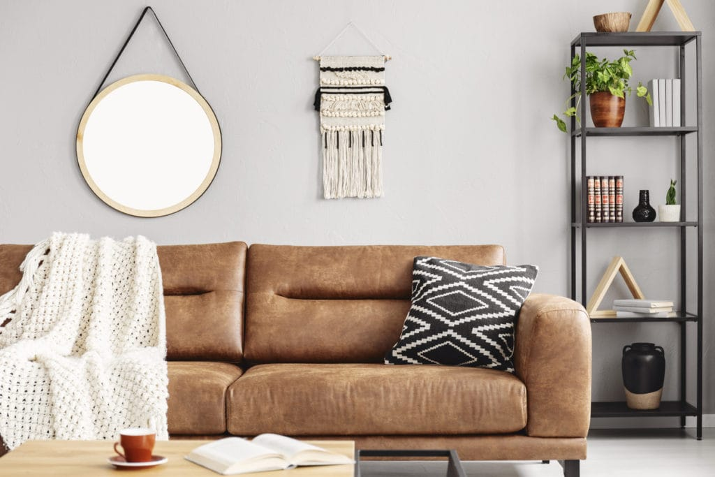 Camel colored brown leather couch accessorized with patterned pillows