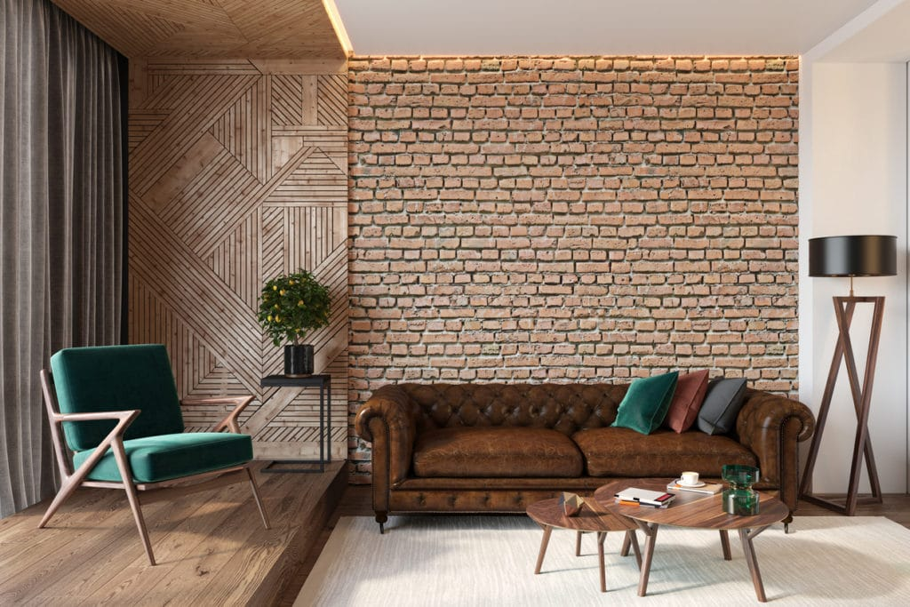 Brown leather couch against a brick wall with a green chair