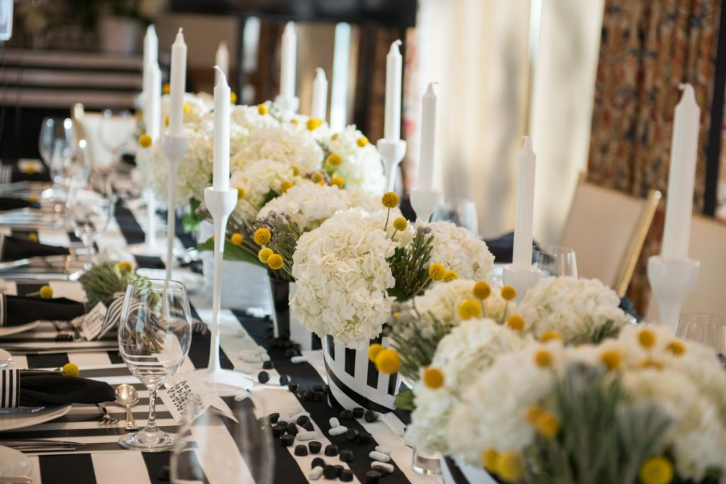 Table with black and white striped tablecloth and white floral centerpieces