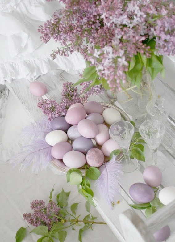 Lilac and pink eggs in a basket with lilac flowers