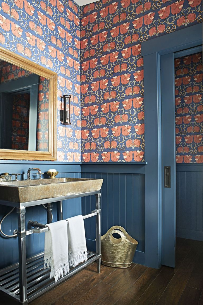 Dark blue wainscoting paired with blue and red wallpaper in a bathroom