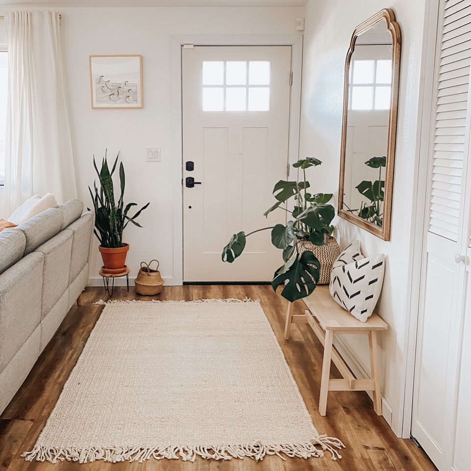 Entry way with houseplants, wooden bench, and natural fiber rug