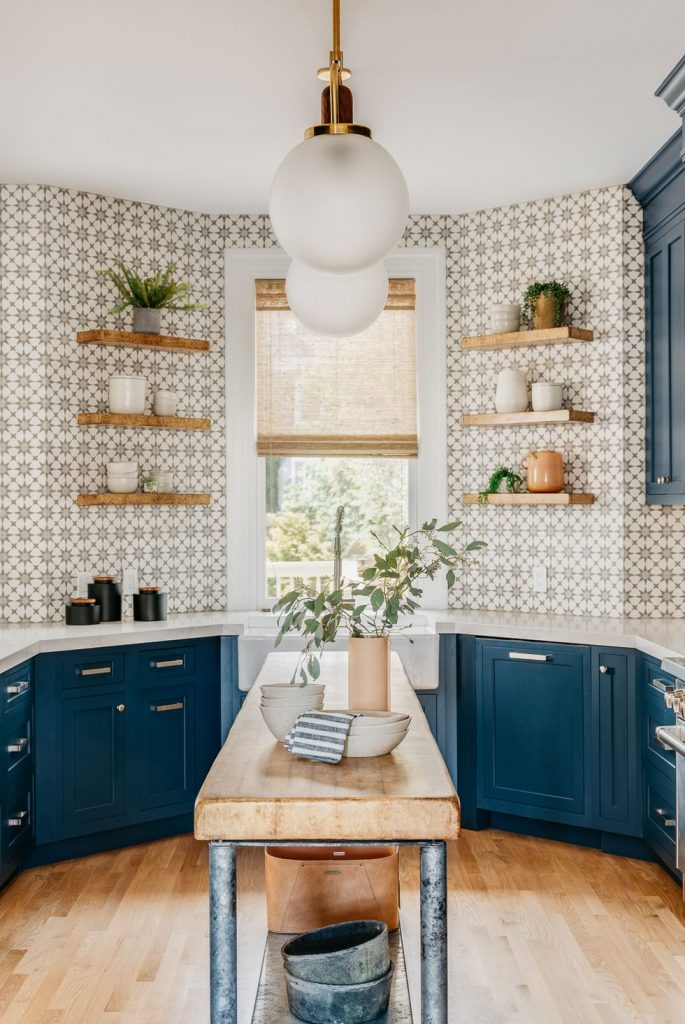 Kitchen with navy cabinets and backsplash tiles with geometric patterns