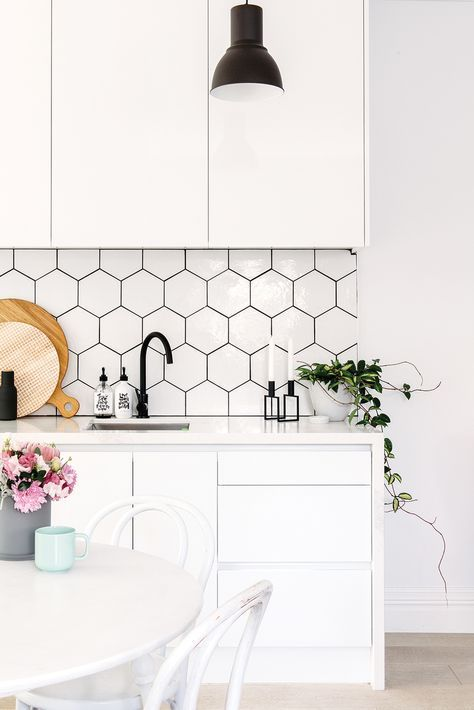 Kitchen backsplash with white hexagon tiles and black grout