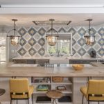 Large kitchen island with yellow chairs and geometric patterned tiles on the backsplash