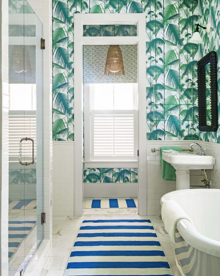 Bathroom with wallpaper patterned with leafy green design and a rug with blue and white stripes.