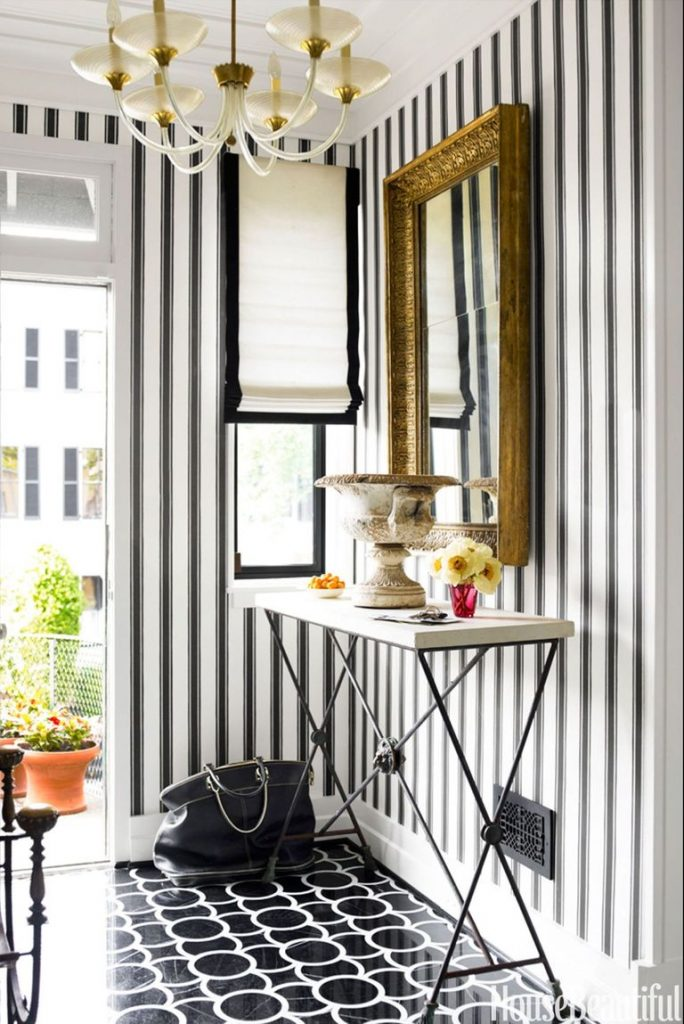 Entryway with black and white striped wall paper, black and white patterned floor, and large gold mirror hanging on wall.