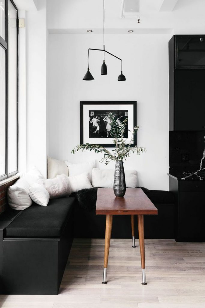 Black banquette area with white throw pillows, black and white framed photo, black pendant lights, and small wooden table with vase on it.