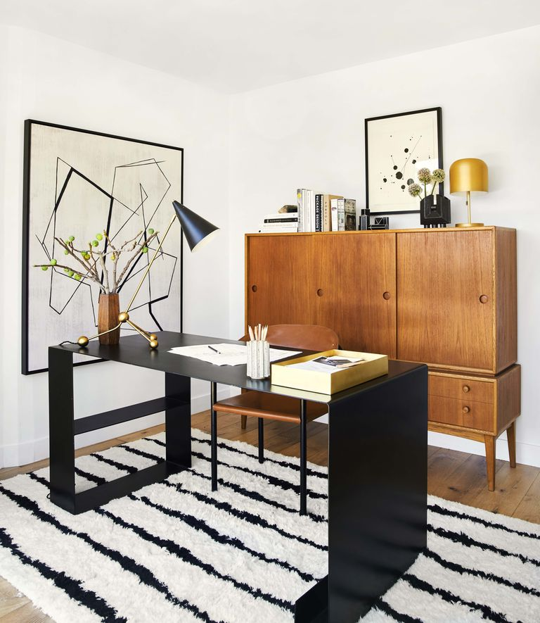 Home office with wooden furniture, framed artwork, sleek black desk, and black and white rug.