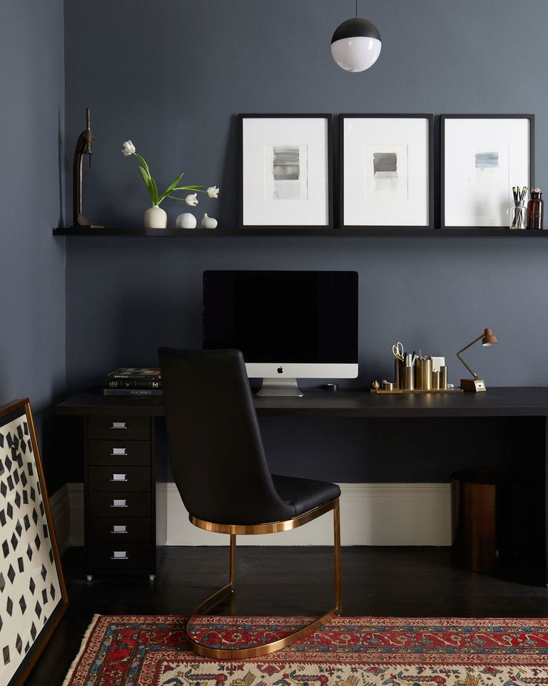 Sophisticated home office with stylish pendant light, framed artwork, black desk, gold details, and navy wall.