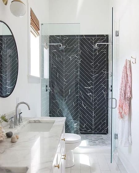 A bathroom with a black color scheme: white with black geometric shower wall.