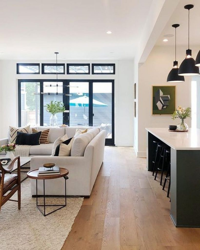 Open living area with black window and door frames, neutral couch, wood floor, and kitchen island with black pendant lights and barstools.