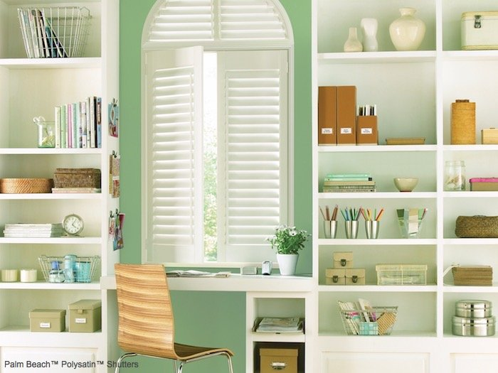 A small desk area with a bright green accent wall surrounded with white bookshelves.