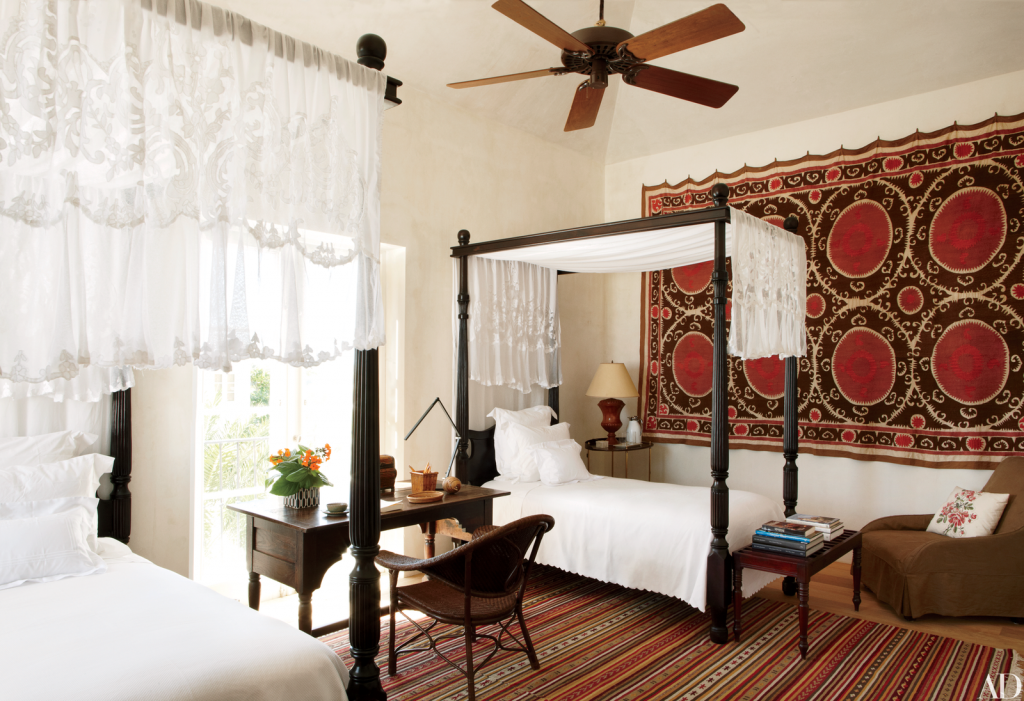 Guest bedroom with two small twin canopy beds, a small desk, ethnic rug, and Turkish tapestry on the wall.