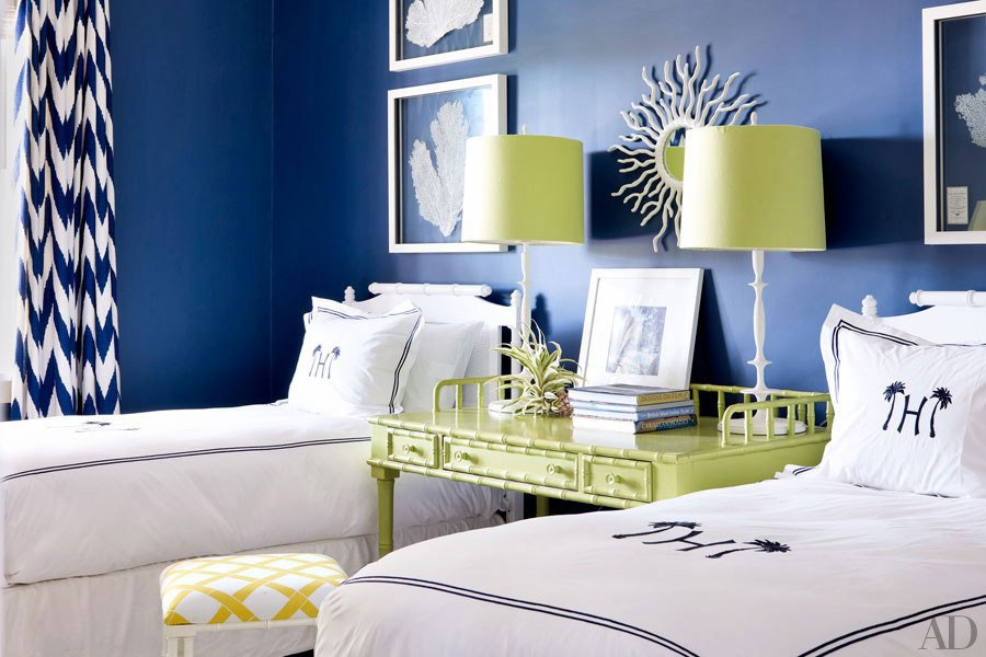 Coastal style bedroom with two twin beds, lime green desk and lamps in between, and rich blue walls.