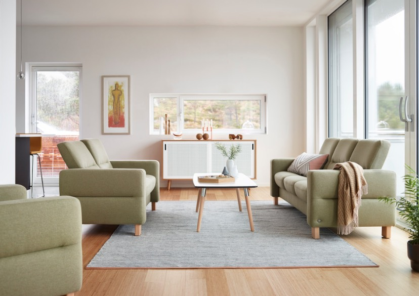Living room with light green sofas, light colored wood, and gray rug.