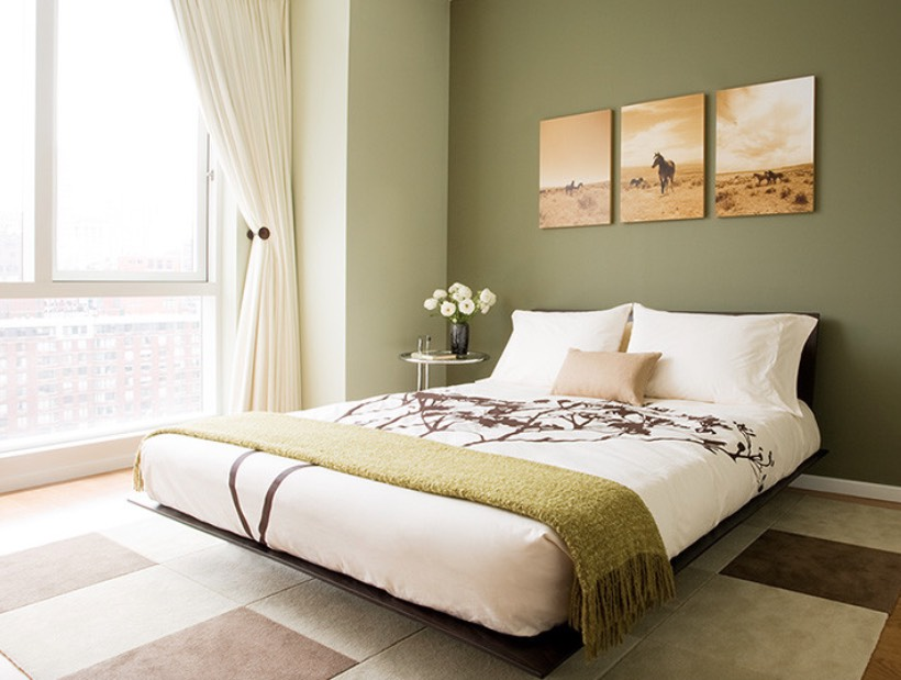 Bedroom with an olive green accent wall behind the bed and green throw on the bed.