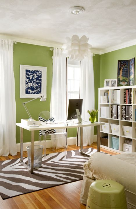 Home office with white desk, bright green accent wall with white trim, white sheer curtains, funky white pendant light, and zebra print rug.