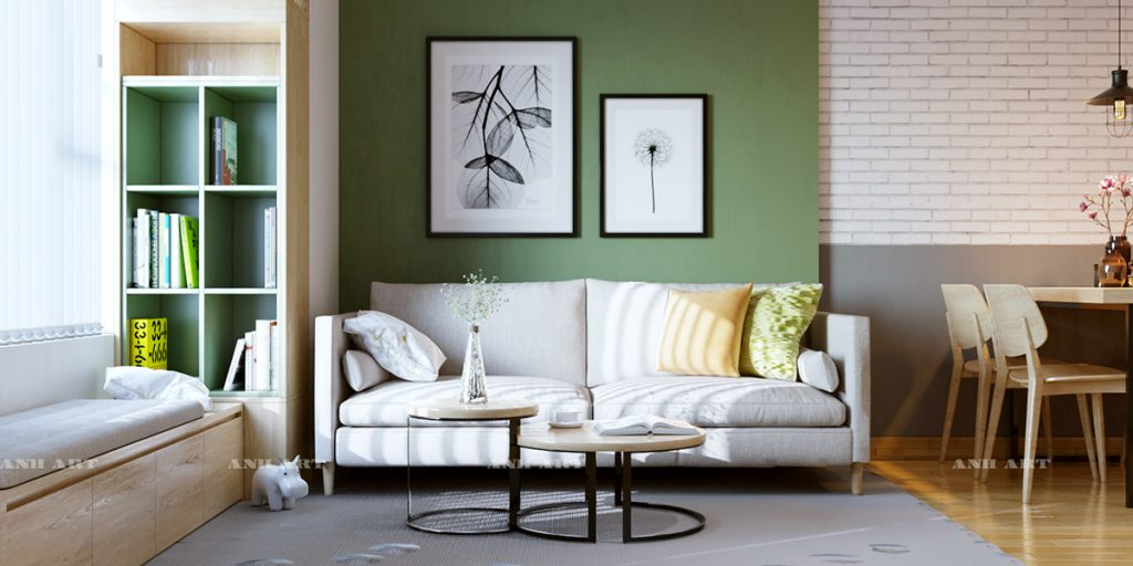A living room with a neutral colored couch against a green accent wall with framed art above near bookshelf with green interior.