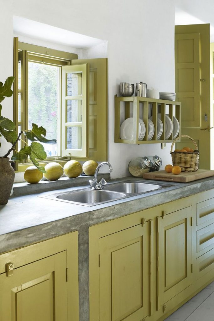 A kitchen with gray countertops and light green cabinetry with matching green window frames, plate rack, and door.