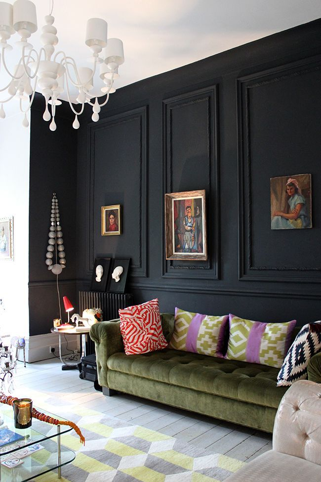 Living room with black wall with molding, green tufted couch, and patterned pillows and rug.