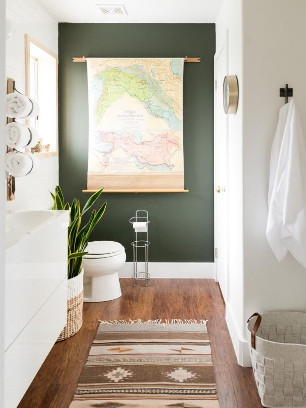 Bathroom with deep olive accent wall with map scroll, medium toned wood floor, aztec rug, and snake plant.