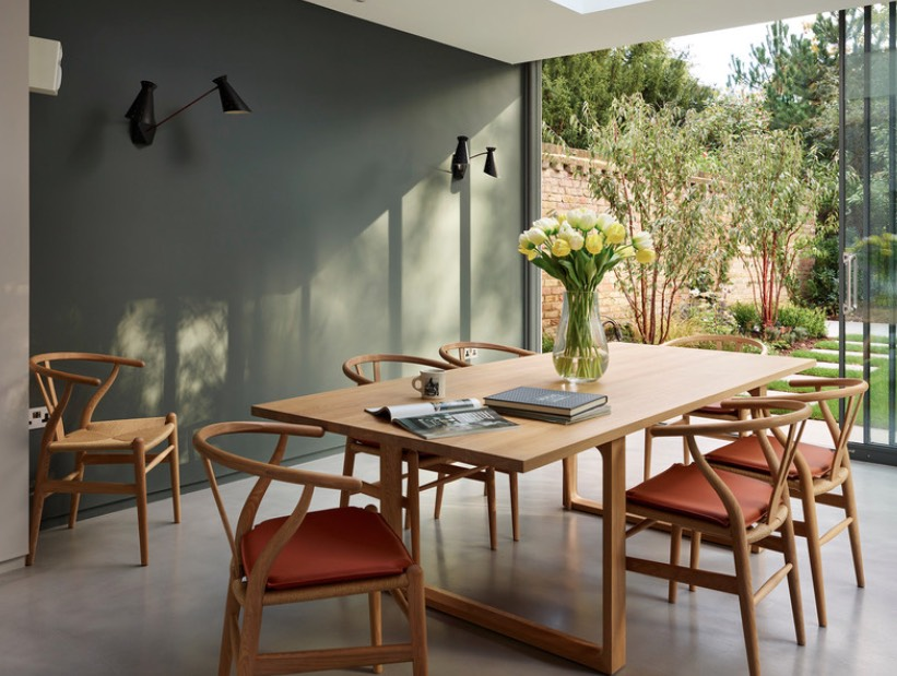 A dining room with a rich olive wall and wooden dining set nearby open sliding doors with an outdoor view.