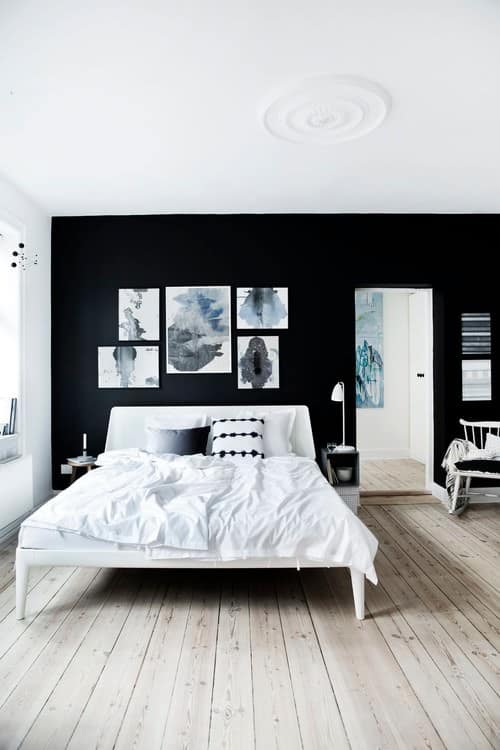 Scandanavian style room with black color scheme: black accent wall, framed art, white bed with white bedsheets, and light wood flooring.