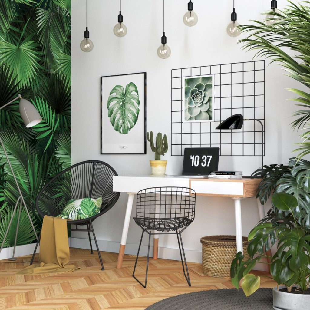Tropical workspace with simple desk, realistic palm wallpaper, plants, botanical artwork, herringbone wooden floors, and hanging light bulb fixtures.