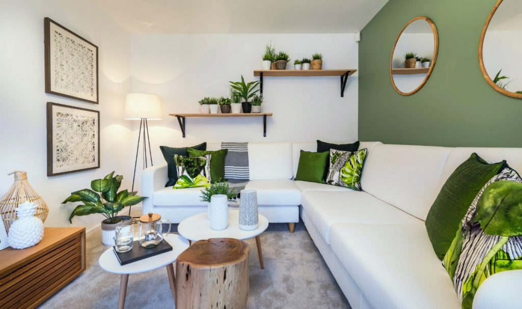 A living room with green accent walls with gold decorative mirrors, a bright white sectional, green solid and graphic pillows, and plants.