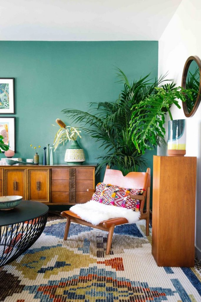 A boho style room with bluish green wall, tropical plant, chair with decorative pillow, and patterned rug.