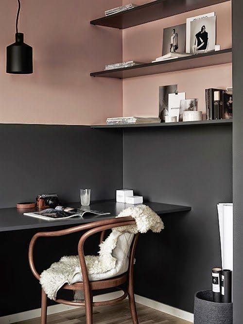 Small office corner with black and pink two-toned walls, black desk, black shelving, and black pendant light.