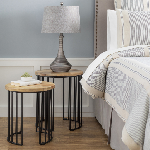 A nesting table set with black metal bases and wooden table tops in staggered heights next to a bed; one has a lamp on it.