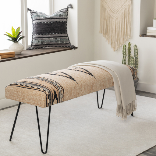 A decorative bench with hand-woven pattern and hairpin legs over a white rug nearby a window seat.