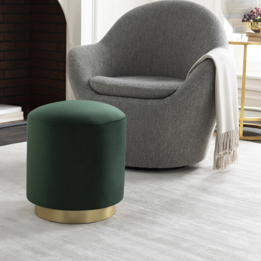 A gray chair with a white throw behind a velvet green ottoman with a gold base.