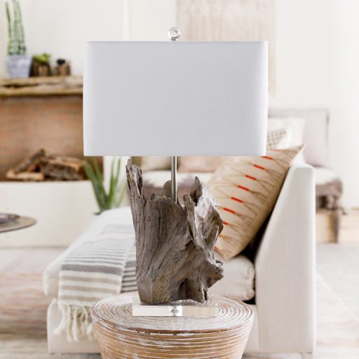 Close up of a table lamp with a modern white lampshade and finished raw wood piece as the base.