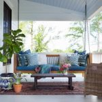 Front porch with porch swing, coffee table, chair, rug, and plants.