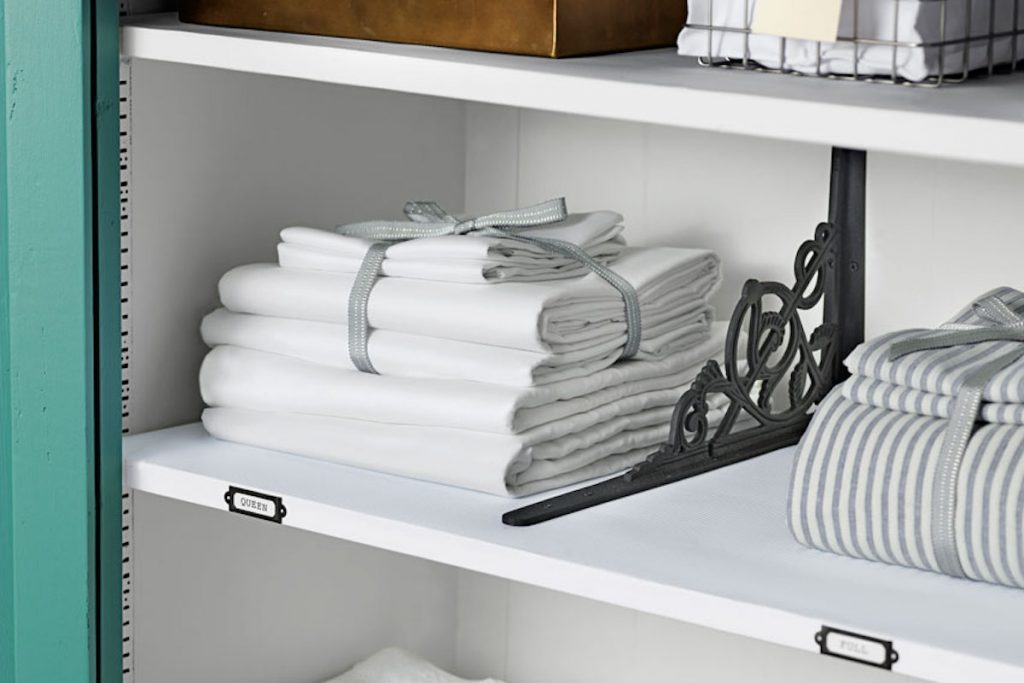Zoomed in shelf of a linen closet with bedsheet sets tied with ribbon.
