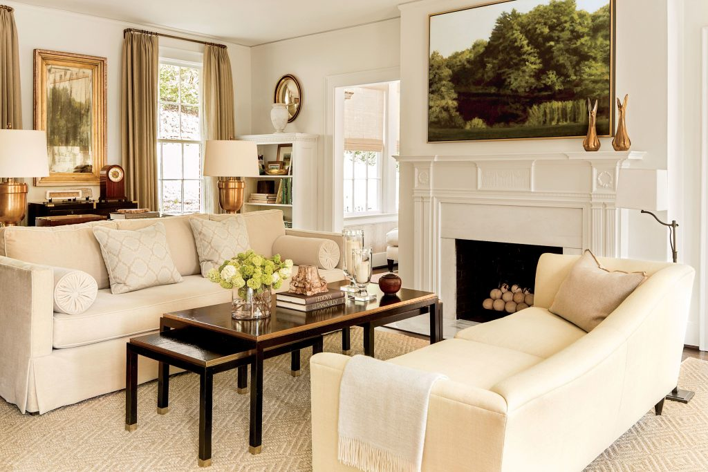 Living room with Acadia White walls, neutral sofas, and dark wooden coffee tables.